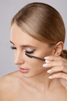 Portret van mooie blondevrouw die mascara met borstel toepassen. natuurlijke make-up. lange wimpers.