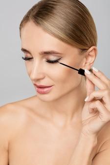 Portret van mooie blondevrouw die vloeibare eyeliner met borstel toepassen. natuurlijke make-up.