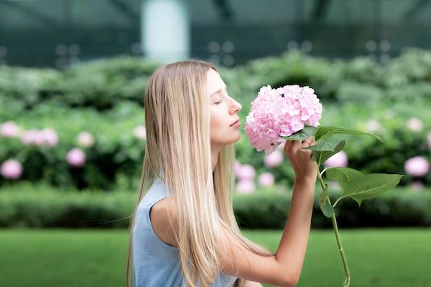 Portret van mooie blondevrouw het snuiven hydrangea hortensiabloem in het park