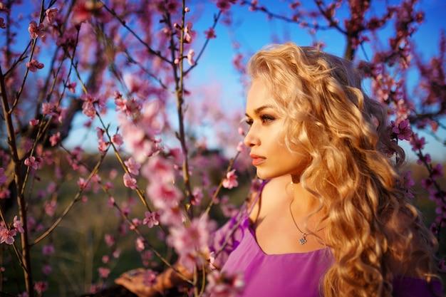 Portret van mooie blondevrouw in bloeiende roze tuin