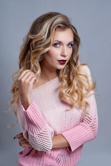 Portret van mooie blondevrouw met krullend kapsel en heldere make-up.