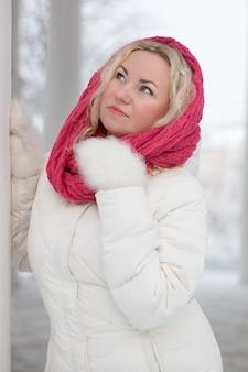 Portret van mooie blondevrouw onder sneeuwval