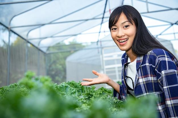 Portret van mooie boer staande in biologische boerderij gewas in de ochtend te onderzoeken.