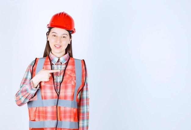 Portret van mooie bouwvakker wijzend op een witte achtergrond.