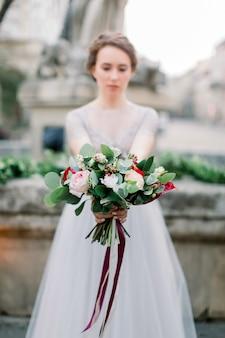 Portret van mooie bruid die in verbazende huwelijkskleding teder boeket houden terwijl status in openlucht op de achtergrond van steenmonument in oud stadscentrum. focus op het boeket