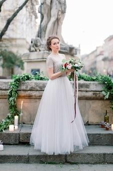 Portret van mooie bruid in geweldige trouwjurk met tedere boeket terwijl je buiten in de trap. oude stadscentrum, lviv, oekraïne