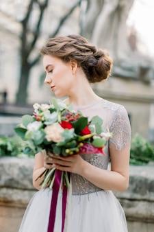 Portret van mooie bruid in het boeket van de de kledingholding van het luxehuwelijk terwijl standig in openlucht in de treden. oude stad, bruiloft