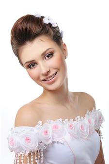 Portret van mooie bruid in trouwjurk op wit wordt geïsoleerd
