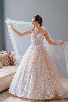Portret van mooie bruid in witte vintage jurk met sluier poseren met de handen uit elkaar