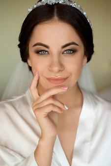 Portret van mooie bruid met maniersluier het stellen op bed bij huwelijksochtend. verzinnen. brunette meisje trouwsluier.