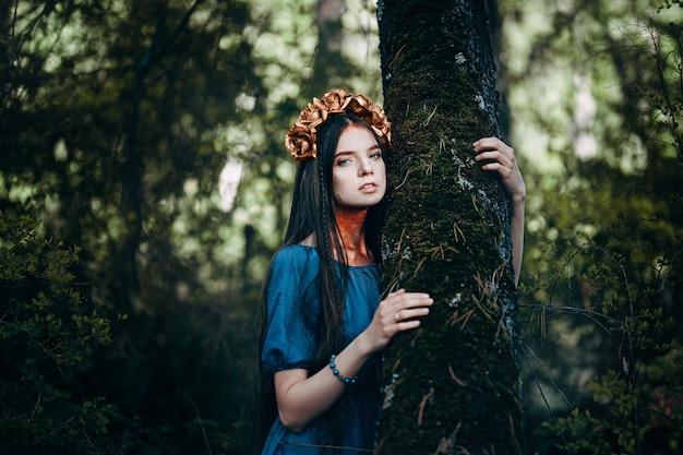 Portret van mooie bruinharige vrouw in blauwe jurk, met een kroon van gouden rozen fee bos