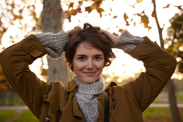 Portret van mooie bruinogige jonge brunette vrouw met natuurlijke make-up met opgeheven handen op haar hoofd terwijl ze positief kijkt met zachte glimlach, buiten poseren in cos warme kleding