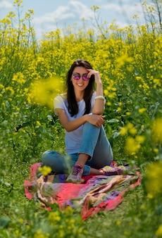 Portret van mooie brunette in zonnebril, zit in koolzaad veld. verticaal schot.