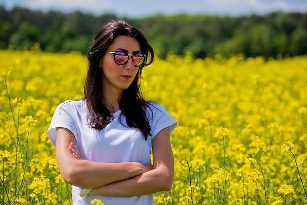 Portret van mooie brunette in zonnebril, zit in koolzaad veld.