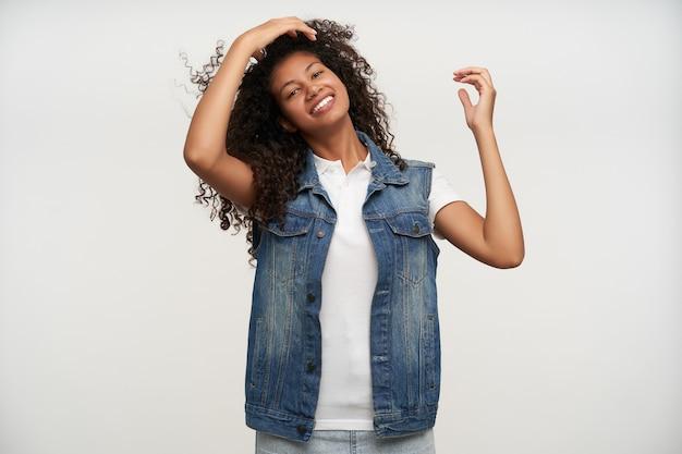 Portret van mooie brunette krullende vrouw met donkere huid haar haren rechttrekken met opgeheven hand en vrolijk kijken, gekleed in spijkerbroek vest en wit overhemd op wit