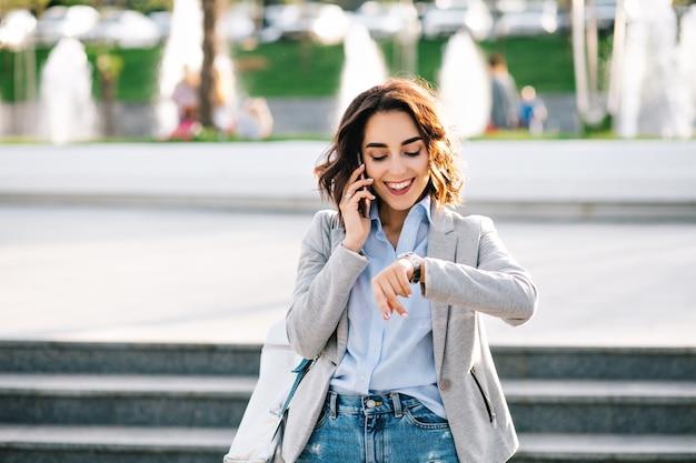 Portret van mooie brunette meisje met kort haar wandelen in de stad. ze draagt een overhemd, een spijkerbroek, een jas en een tas. ze praat aan de telefoon, kijkt naar het horloge en lacht.