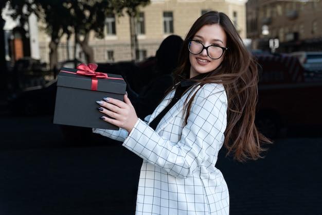 Portret van mooie brunette meisje met zwarte geschenkdoos in haar handen. gelukkig stijlvol meisje houdt doos met rode strik.