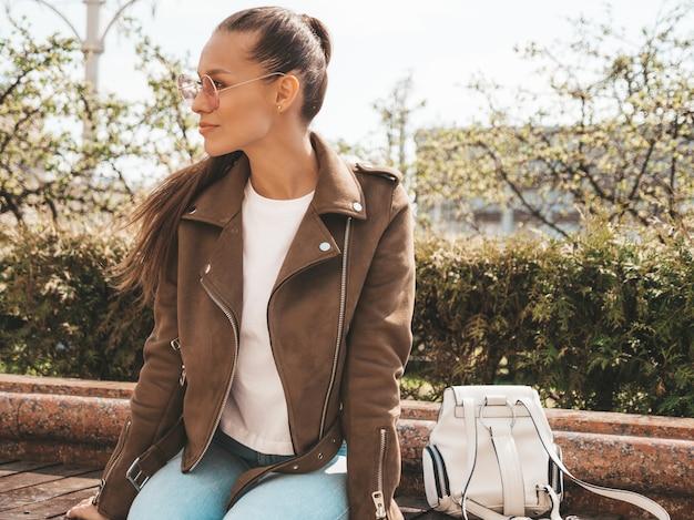 Portret van mooie brunette model gekleed in zomer hipster jas en jeans kleding trendy meisje, zittend op de bank in de straat