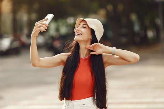 Portret van mooie brunette. model in zomerstad. vrouw loopt met mobiele telefoon.