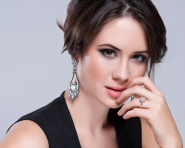 Portret van mooie brunette vrouw in zwarte jurk. cosmetische oogschaduw.