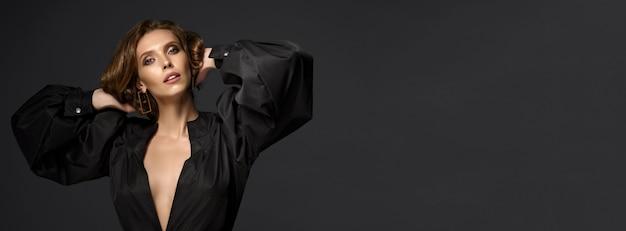 Portret van mooie brunette vrouw in zwarte jurk