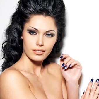 Portret van mooie brunette vrouw met blauwe nagels