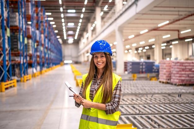 Portret van mooie brunette vrouw met veiligheidshelm en reflecterende jas met controlelijst in groot magazijn opslagruimte