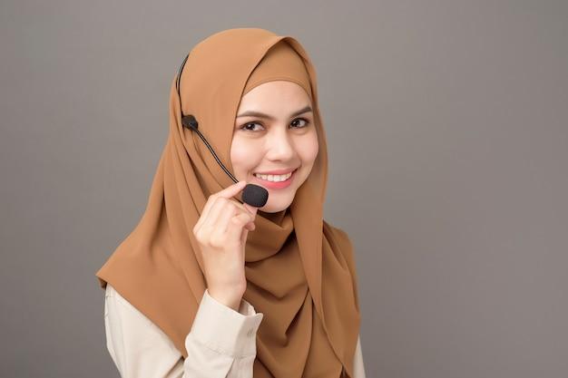 Portret van mooie call centrevrouw met hijab op grijs