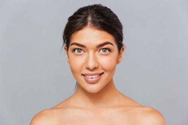 Portret van mooie charmante jonge brunette vrouw met perfecte huid over grijze muur