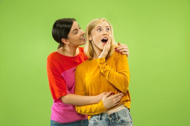 Portret van mooie charmante meisjes in casual outfits geïsoleerd op groene muur. twee vrouwelijke modellen als vriendinnen of lesbiennes. concept van lgbt, gelijkheid, menselijke emoties, liefde, relatie.