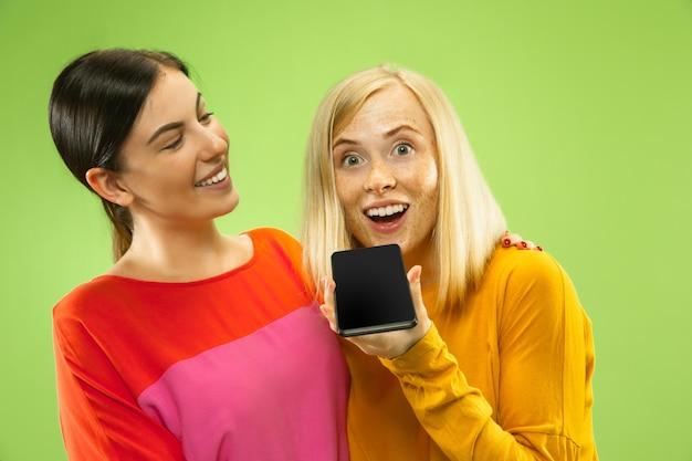 Portret van mooie charmante meisjes in casual outfits geïsoleerd op groene muur. vriendinnen of lesbiennes praten over smartphone. concept van lgbt, gelijkheid, menselijke emoties, liefde, relatie.