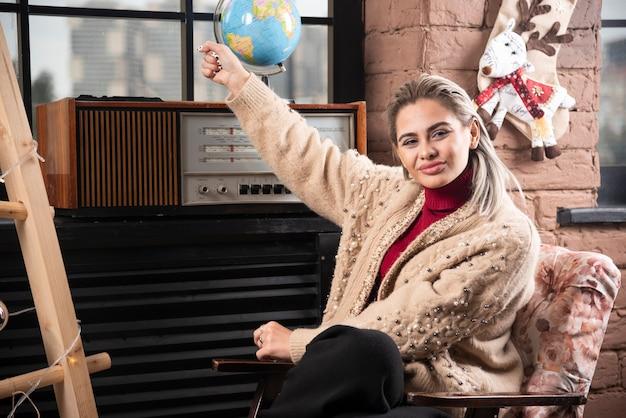 Portret van mooie dame die een wereldbol tegenhoudt
