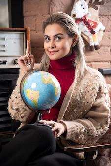 Portret van mooie dame die omhoog wijst en een wereldbol vasthoudt