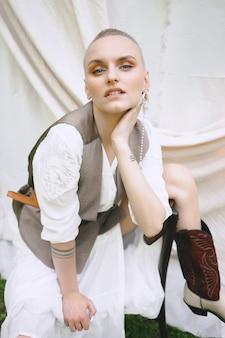 Portret van mooie dame in de tuin met witte muur zitten en kijken in witte en grijze jurk overdag.