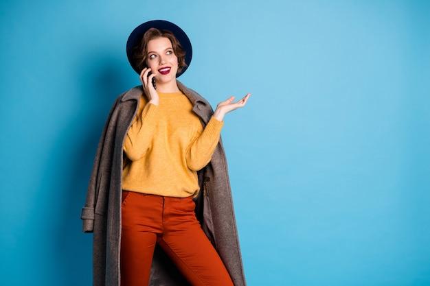 Portret van mooie dame lopen straatreiziger sprekende telefoon met vrienden vertellen adres om te gaan dragen casual lange grijze jas pullover broek hoed schoenen.