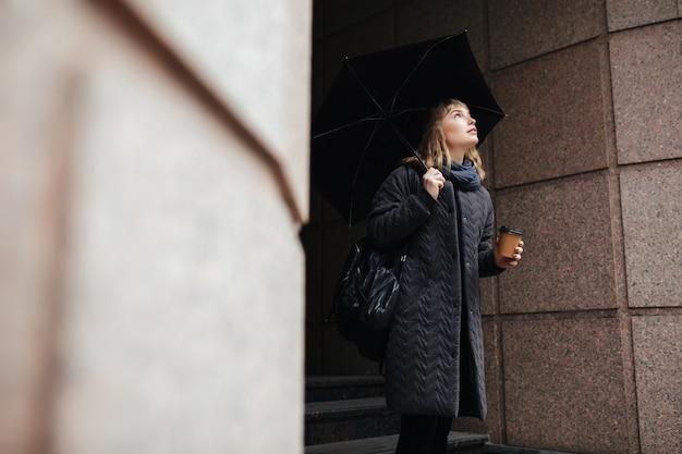 Portret van mooie dame staande op straat met zwarte paraplu en koffie in handen terwijl dromerig opzoeken