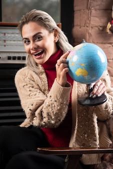 Portret van mooie dame wijzend op een wereldbol