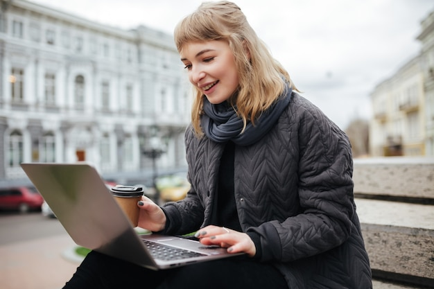 Portret van mooie dame zitten en gelukkig kijken in laptop met koffie in de hand op straat in de stad