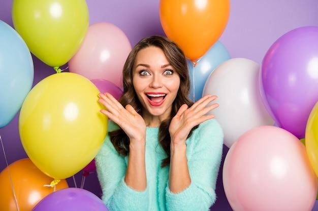 Portret van mooie damehanden die dichtbij wangen worden opgeheven omringd vele kleurrijke luchtballons die zwarte vrijdag-opening aankondigen, dragen pastelkleurige fuzzy pullover.