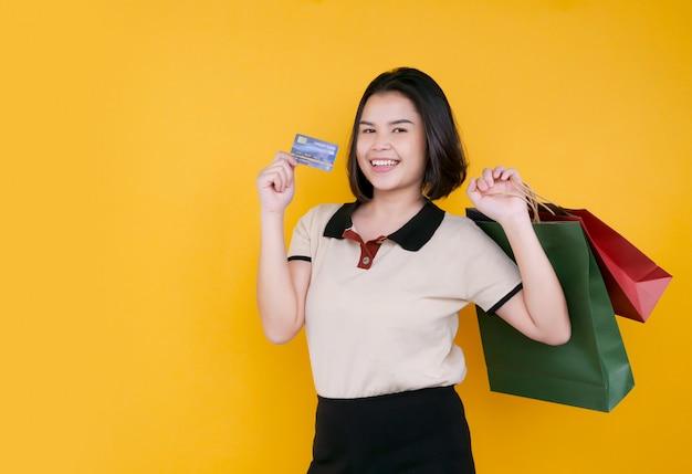Portret van mooie de creditcard en het winkelen van de meisjesholding zakken.