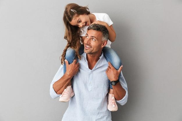 Portret van mooie dochter glimlachend en zittend op de nek van haar knappe vader, geïsoleerd over grijs