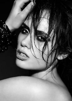 Portret van mooie donkerbruine jonge vrouw met natte huid en haar