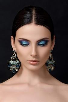 Portret van mooie donkerbruine vrouw met blauwe oorringen die zich voordeed op zwarte achtergrond.