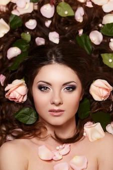 Portret van mooie donkerbruine vrouw met lang krullend haar en heldere make-up witjh bloemen in haar
