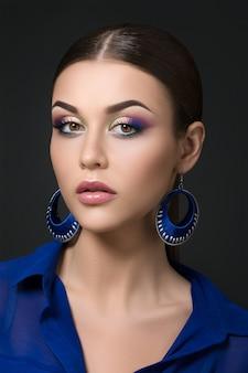 Portret van mooie donkerbruine vrouw met maniersamenstelling en blauwe oorringen