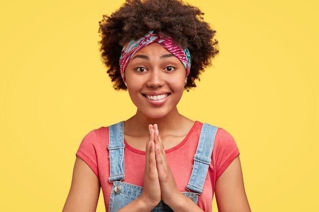 Portret van mooie donkere huid vrouw met knapperig haar, heeft een smekende uitdrukking, houdt de handen in gebed gebaar, draagt denim tuinbroek breed glimlacht, geïsoleerd over gele muur. lichaamstaal