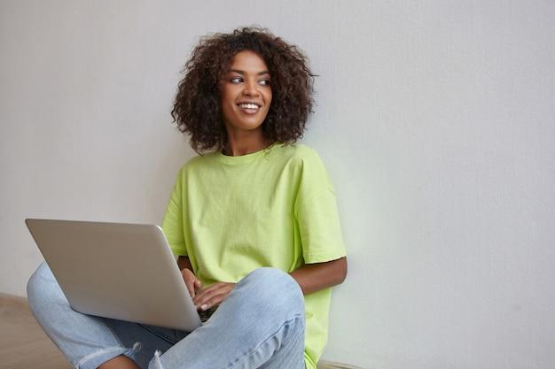 Portret van mooie donkere vrouw met bruin krullend haar poseren over witte muur, opzij kijken met charmante glimlach, laptop op benen houden met handen op toetsenbord