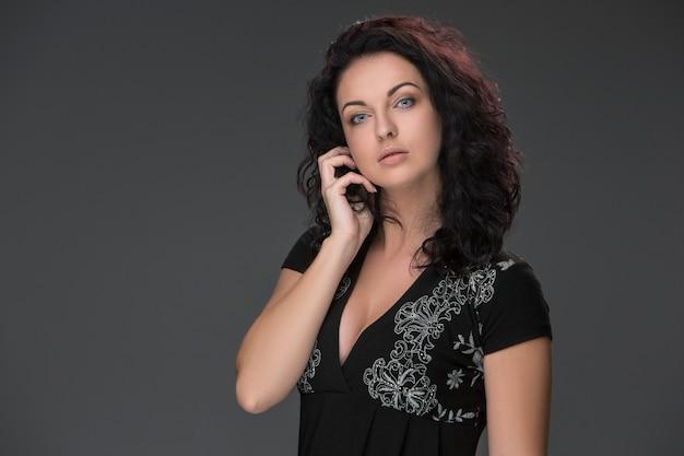 Portret van mooie donkerharige jonge vrouw, spreken op mobiele telefoon