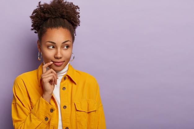 Portret van mooie doordachte krullende vrouw houdt wijsvinger in de buurt van de lippen, kijkt opzij, merkt iets aan de rechterkant, draagt oorbellen en stijlvolle kleding, vormt tegen een violette achtergrond.