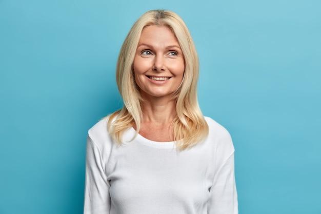 Portret van mooie dromerige blonde vrouw van middelbare leeftijd met tevreden gezichtsuitdrukking voelt goed herinnert aan mooie herinneringen geconcentreerd boven draagt casual witte trui poses